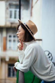 Young in white sweater and hat staying at balcony