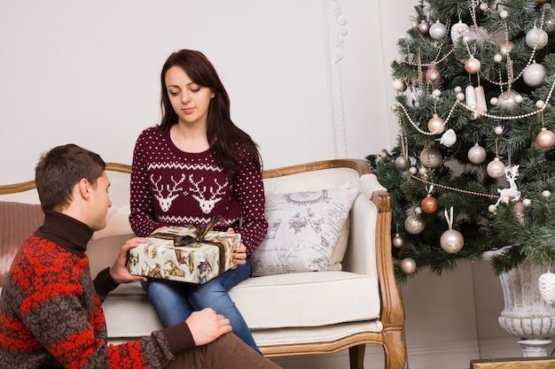 リビングルームのクリスマスツリーの装飾の近くにギフトボックスを保持しているカジュアルな冬のシャツの若い白い恋人。