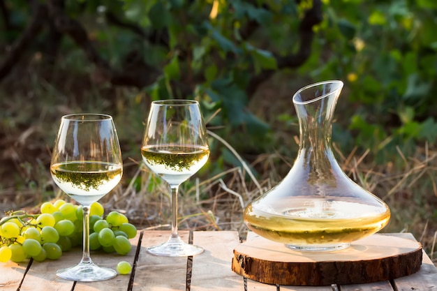 Young white wine on nature, decanter and white grapes