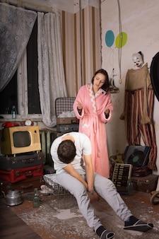 ピンクのローブの若い白人女性は、乱雑な放棄された部屋でケージに座っている彼女の眠っているパートナーにイライラしました。