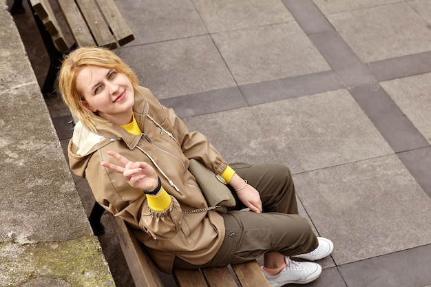 Young white woman shows two-finger victory sign while sitting on park bench in cold season, top view.