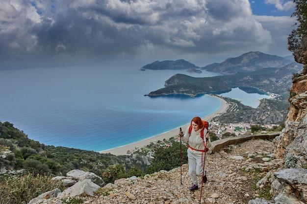 젊은 백인 여자는 그녀가 터키의 올 루데 니즈의 리조트 마을 근처에서 라이 키아 길을 올라갈 때 지팡이를 사용합니다.