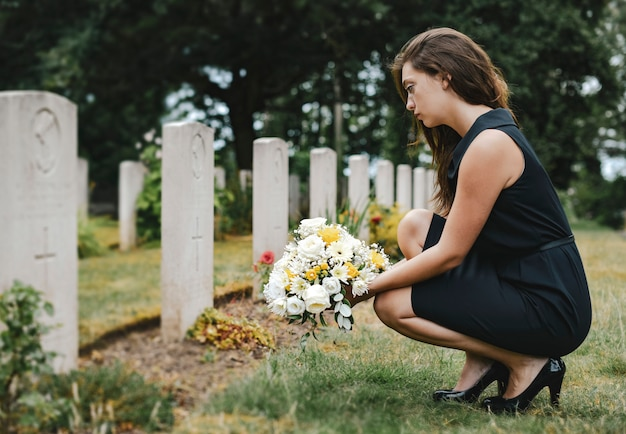 Young widow laying flowers at the grave Premium Photo