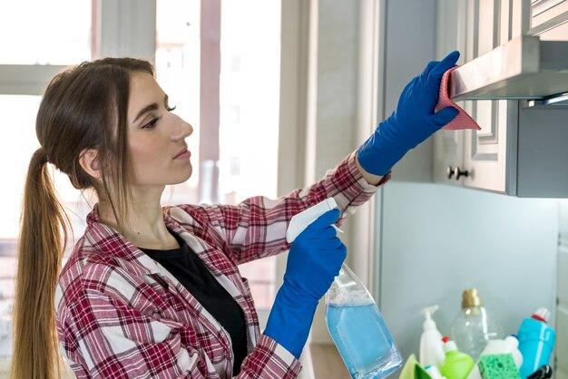台所でぼろきれと洗剤で炊飯器のフードを掃除する若い妻。ハウスキーピングのコンセプト。