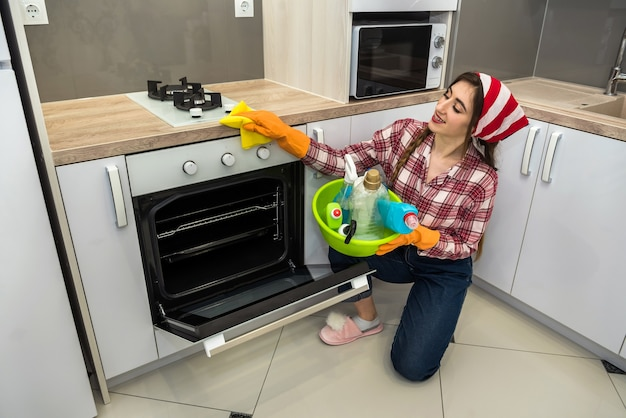 Young wife cleaning oven with yellow rag and spray in kitchen.