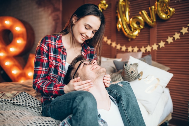 Young wife and husband hugs on the bed in bedroom with lighting decoration. love couple in clothes embrace on couch