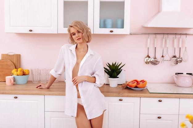 Молодая жена. сексуальная красивая молодая жена в белых трусиках и рубашке стоит на кухне