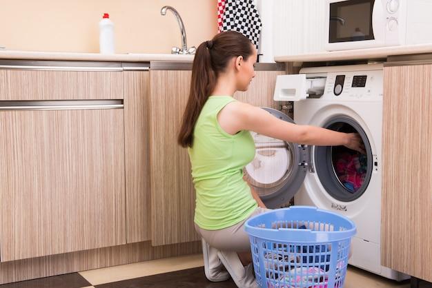 Young wife woman washing clothes near machine