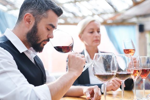 Молодой кузнец винодельни нюхает красное вино в одном из бокалов при проверке качества различных сортов