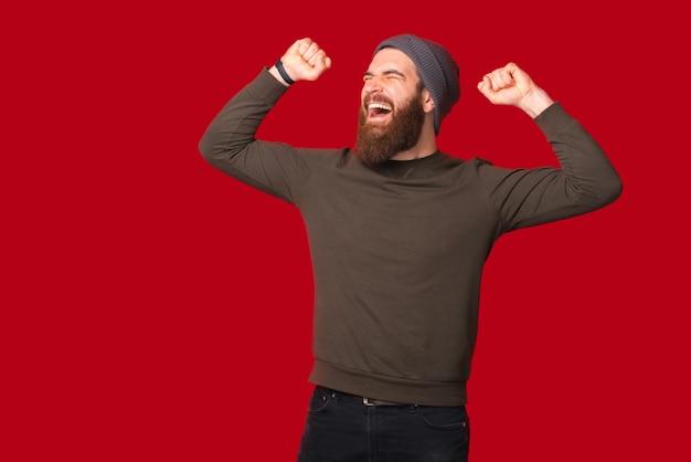 若い勝者のひげを生やした男は、叫びながら腕を上げて身振りで示しています。