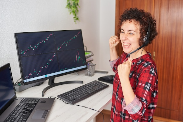 Молодая успешная бизнес-леди, смотрящая на экраны, празднует успех успешной операции