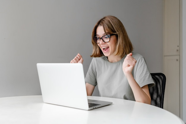 Young winning caucasian woman taring at laptop in the apartment