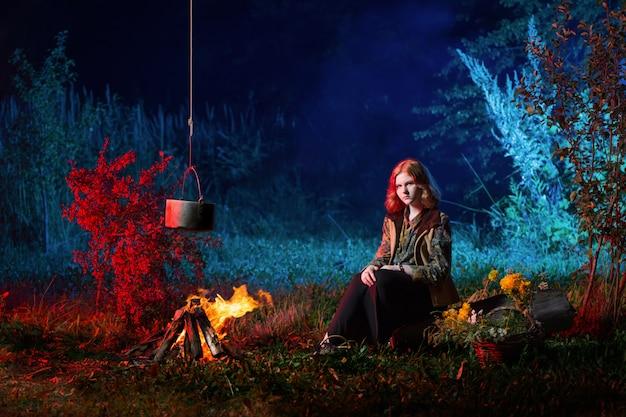 夜の森で火事で若い魔女は魔法のポーションを準備します