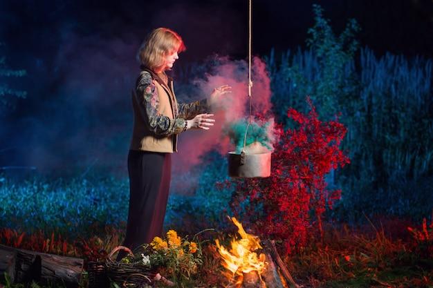 夜の森の火で若い魔女は魔法のポーションを準備します