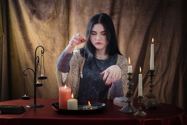 Young witch conjures with burning candles on dark surface