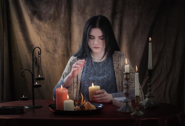 젊은 마녀는 어두운 표면에 촛불을 굽기