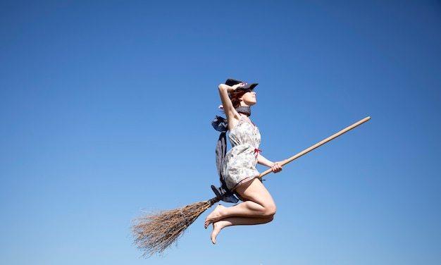 Young witch fly on a broom in a sky