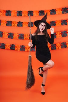 Young witch girl in black halloween costume holding broom isolated over orange pumpkin wall