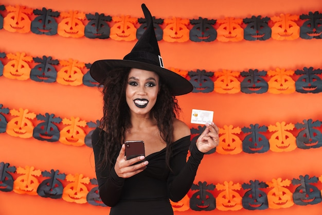 Young witch girl in black halloween costume holding smartphone and credit card isolated over orange pumpkin wall