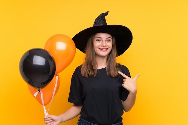 驚きの表情でハロウィーンパーティーのための黒とオレンジの気球を保持している若い魔女