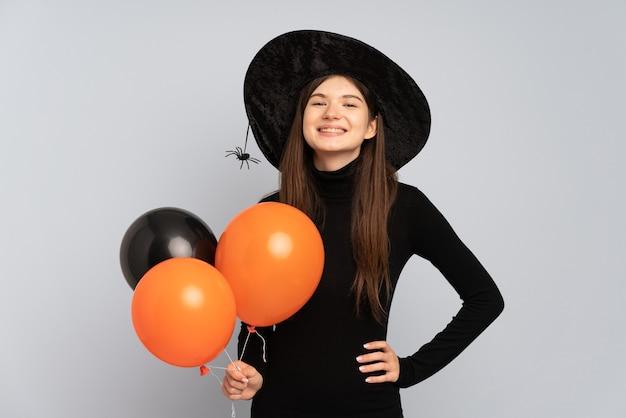 黒とオレンジの気球を保持している若い魔女