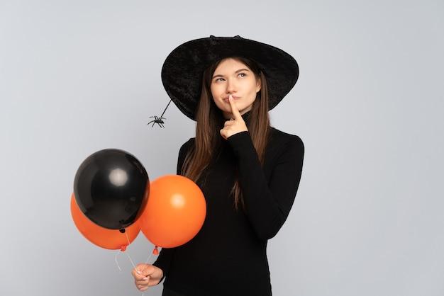 Молодая ведьма держит черные и оранжевые воздушные шары