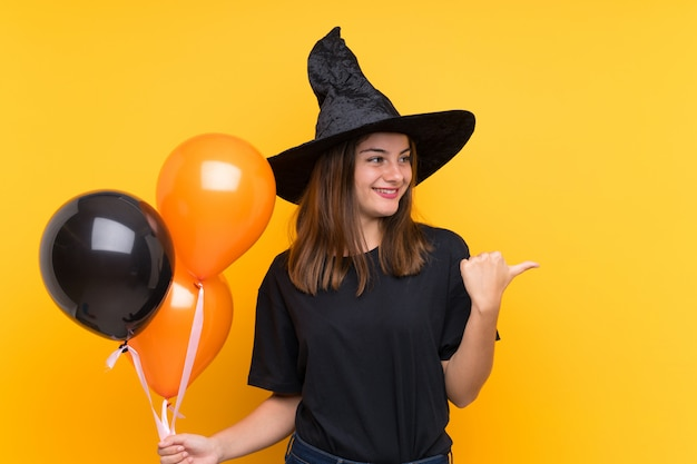 Young witch holding black and orange air balloons for halloween parties pointing to the side to present a product