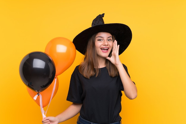 Young witch holding black and orange air balloons for halloween parties shouting with mouth wide open