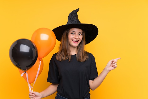Young witch holding black and orange air balloons for halloween parties surprised and pointing finger to the side