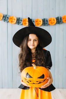 Young witch holding pumpkin at Halloween party