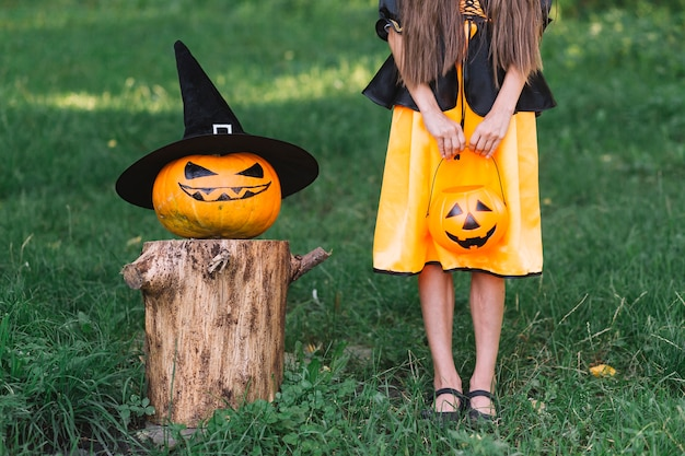 Young witch and jack-o-lantern standing in forest on halloween