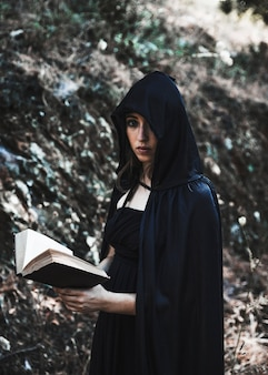Young witch with book in thicket