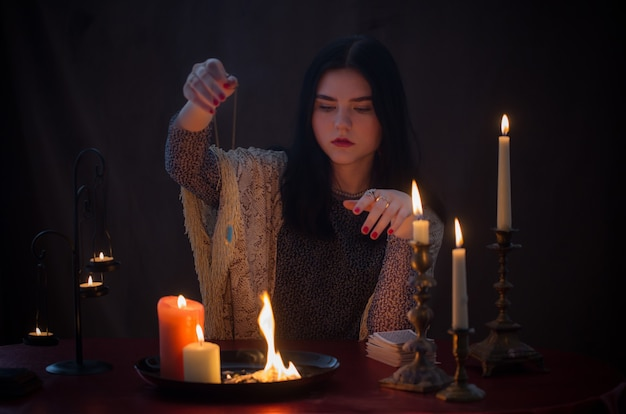 Young witch with fire and burning candles on dark surface