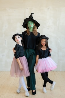 Young witch with her face painted green embracing two girls