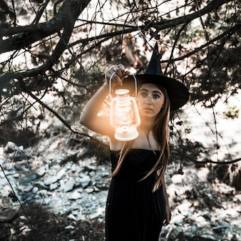 Young witch with lamp illuminating path in thicket daytime