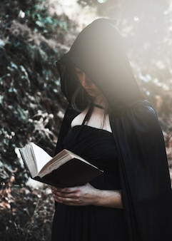 Young witch with opened book in sunlit thicket