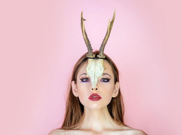 若い魔女。女性の魔女、ハロウィーン。動物の頭蓋骨と枝角を持つ女性の美しさ。
