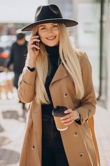 Молодая женщина со светлыми волосами в черной шляпе разговаривает по телефону и пьет кофе