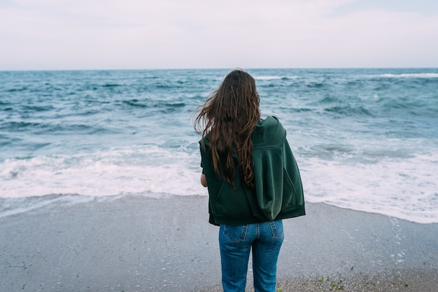 若い女性が海の波をスマートフォンで撮影