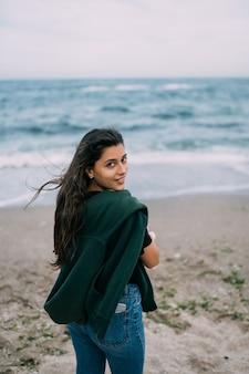Молодая женщина снимает на смартфон морские волны