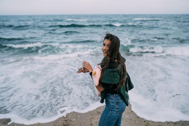若いウォマがスマートフォンで海の波を撃つ