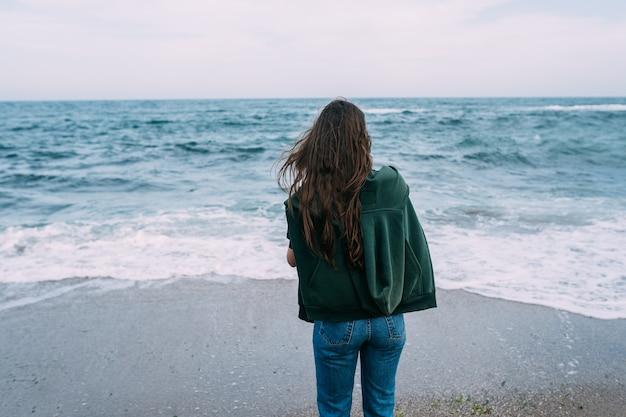 Il giovane woma spara su uno smartphone le onde del mare