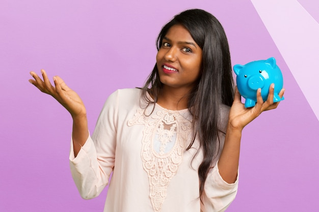 Young woman 20s in casual clothing holding piggybank with lots of money isolated