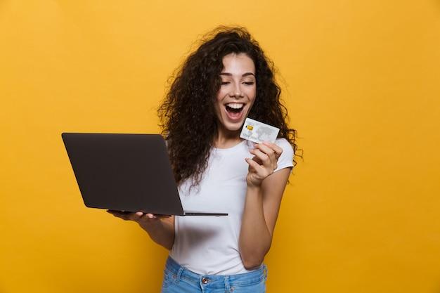 Молодая женщина 20 лет в повседневной одежде держит черный ноутбук и кредитную карту, изолированную на желтом