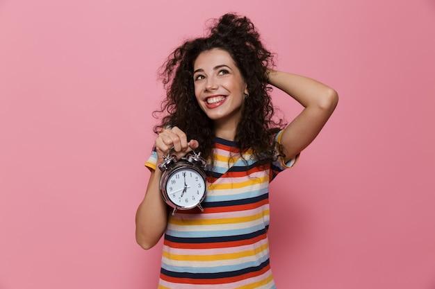 ピンクで隔離の目覚まし時計を保持している巻き毛の若い女性20代