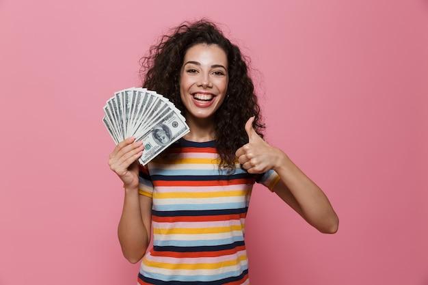 ピンクに分離されたドルのお金のファンを保持している巻き毛の若い女性20代
