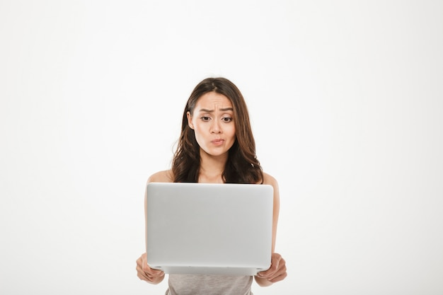 Young woman 30s looking on screen of her silver notebook thinking or expressing misunderstanding with face, isolated over white wall