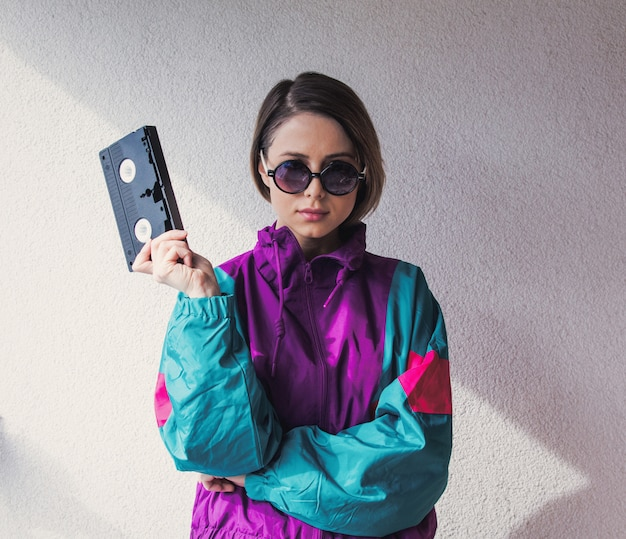 Young woman in 90s style clothes holding vhs cassette