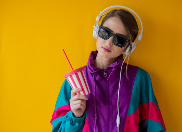 Young woman in 90s style clothes with cup and headphones