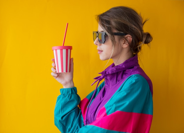 Young woman in 90s style clothes with cup